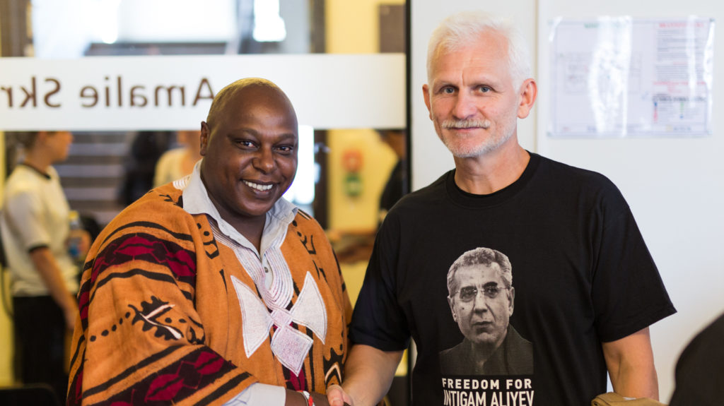 "Former political prisoner in Belarus, Ales Bialiatski, Head of the Human Rights Centre ""Viasna"", wearing a t-shirt calling for the release of human rights lawyer Intigam Aliyev in Azerbaijan, pictured with UN Special Rapporteur Maina Kiai, 9 September 2015."