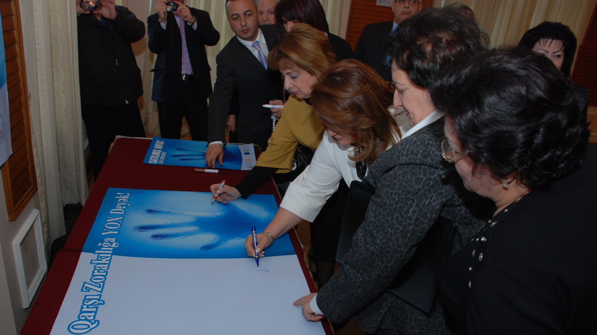 Head of State Committee for Family, Women and Children's Affairs Hijran Huseynova signs the signature poster of WARD to advocate for adoption of Law on Domestic Violence in 2009